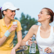 Постер, плакат: Two smiling girl friends in sports clothing drinking water