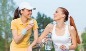 Two smiling girl friends in sports clothing drinking water, — Stock Photo