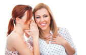 Two happy young girl friends  whispering — Stock Photo