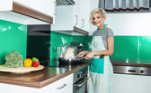 Smile woman cook or housewife holding pan in the kitchen at home — Stock Photo