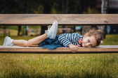 Pleasure little girl lying on bench in a park — Stock Photo