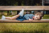 Pleasure little girl lying on bench in a park — Foto de Stock