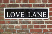 Street Sign For Love Lane On Brick Wall — Zdjęcie stockowe