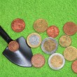 Стоковое фото: Coins, shovel on green background.