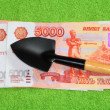 Money and a shovel — Stock Photo