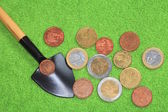 Coins, shovel on a green background. — Stock Photo