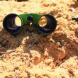 Stock Photo: Binoculars on the sand.