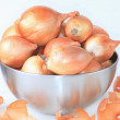 Onions in a bowl, husks. - Stock Photo