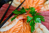 Closeup of raw fish with Japanese chopsticks highlighted — Stock Photo