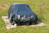 Old car beneath cover — Stock Photo