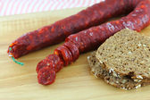 Chorizo with wholewheat bread on a wooden cutting board — Stock Photo