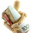 A wooden doll holding a roll of money — Stock Photo