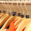 Wooden hangers showing different clothing size tags — Stock Photo #28699773