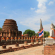 Old Chedi and Buddha Images along ruined cloister, at Wat Yai Chai Mongkol, Ayutthaya — Stock Photo