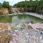 A mountain of dirty trash surrounding the lake — Stock Photo