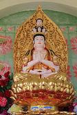 Statue of Avalokitesvara sitting on lotus flower — Stock Photo