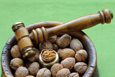 Walnuts in a wooden bowl with a Nutcracker hammer — Stock Photo