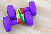Purple dumbbells with measuring tape — Foto Stock