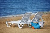 Sunchairs and Packed beach bag on empty sand beach — Stock Photo