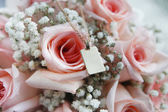 Golden pendant on pink roses — Stock Photo