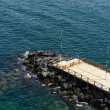 Stock Photo: Wooden pier surrounded by seand rocks