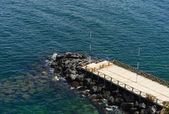 Wooden pier surrounded by the sea and the rocks — Stock Photo