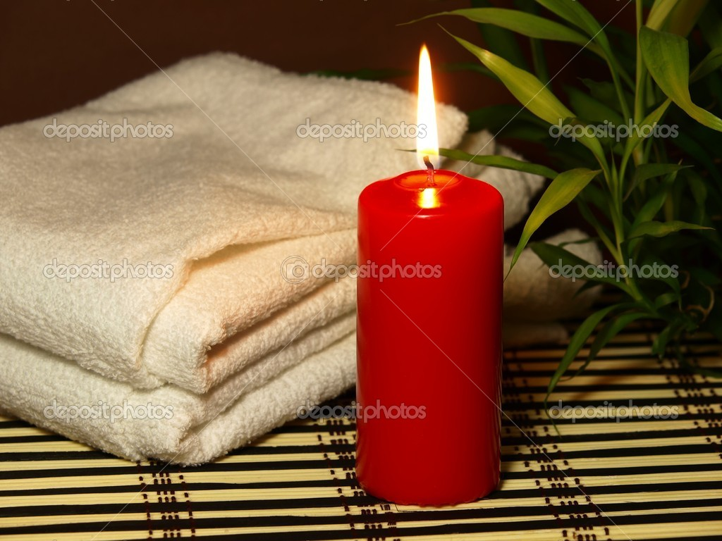 Red candle with towell and bamboo plant on a wooden mat. — Stock Photo #13850438