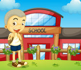 A boy standing near the school — Stock Vector