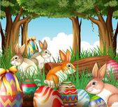 A group of bunnies and easter eggs — Stock Vector
