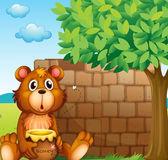 A bear with honey near a pile of bricks — Stock Vector