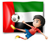 A boy playing soccer in front of the UAE flag — Stock Vector