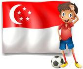Ein fußball-spieler neben der flagge von singapur — Stockvektor