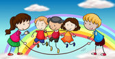 Five kids playing in front of a rainbow — Stock Vector