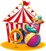 A clown sitting above a ball beside a ring of fire in front of — Stockvector