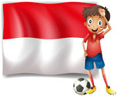 A boy with a soccer ball standing in front of the Monaco Flag — Stock Vector