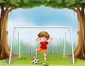 A little soccer player in his red uniform — Stock Vector