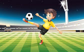A boy in his yellow uniform playing soccer at the field — Stock Vector
