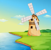 A windmill along the river — Stock Vector
