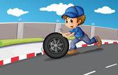 A boy pushing a wheel along the road — Stock Vector