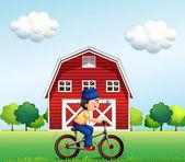 A Muslim boy biking near the barnhouse — Stock Vector