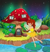 A fairy flying near the red mushroom house — Stock Vector