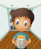 A boy holding a jar of candies in front of the bookshelves — Stock Vector
