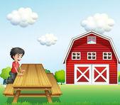 A boy at the table near the barnhouse — Stock Vector