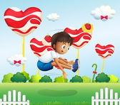 A boy jumping in the field with giant lollipops — Stock Vector