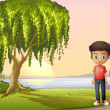 A boy standing near the giant tree — Stock Vector