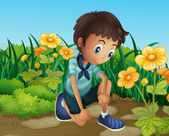 A sad boy near the blooming flowers — Stock Vector
