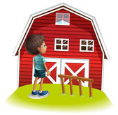 A boy standing in front of the red farmhouse — Stock Vector