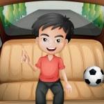 A boy inside the car with a soccer ball — Stock Vector #30988039