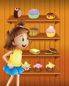 A happy girl in front of the cupcakes and cookies — Stock Vector