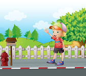 A young boy waving near the mailbox at the road — Stock Vector